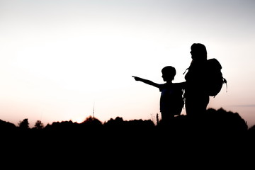 Silhouettes of mother and child hiking at sunset. Boy pointing at something distant. Summer vacation in mountains. Traveling with little kids. Mom and son with backpacks standing on the hill edge.