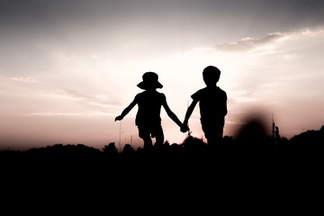 Silhouettes of kids jumping off a hill at sunset. Little boy and girl jump high holding hands. Brother and sister having fun in summer. Friendship, freedom concept.