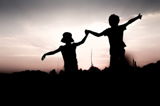 Silhouettes of children jumping off a cliff at sunset. Boy and girl jump high holding hands. Brother and sister having fun in summer. Friendship, freedom concept