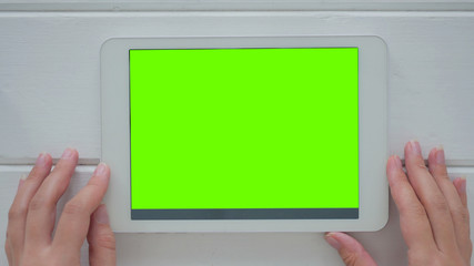 Woman looking at horizontal tablet computer with green screen. Close up shot of woman's hands with pad. Technology and internet concept White wooden background