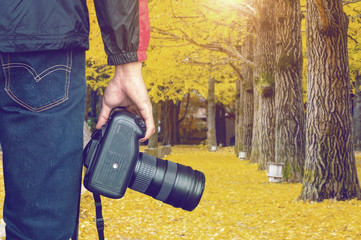 professional photographer with camera in autumn. Vintage tone.