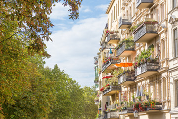 Traditional European residential house with balconys with colorful flowers and flowerpots....
