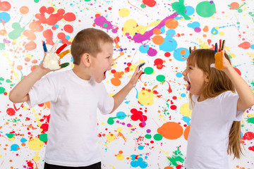 Little boy and girl to paint on his hands shouting at each other