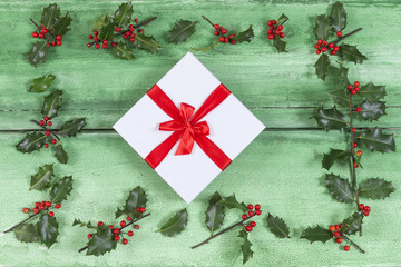 Beautiful Christmas gifts i the middle of Holly on old green  painted cracked wooden background