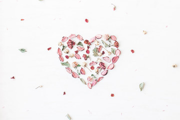 Flowers composition. Heart symbol made of dried flowers and leaves. Top view, flat lay