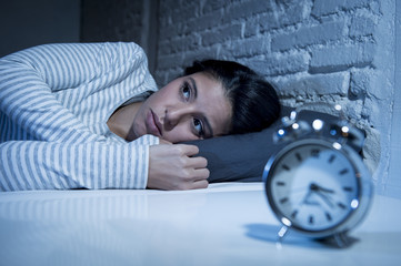 hispanic woman at home bedroom lying in bed late at night trying to sleep suffering insomnia