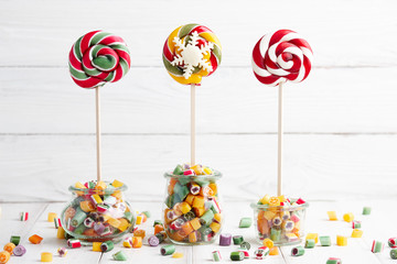 Colorful lollipops and candy canes in glass jars on white wooden background
