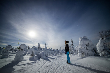 Woman and snow covered trees, Finland