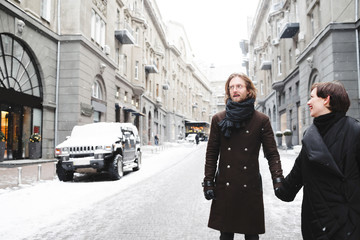 Couple has fun and laughs.  kiss. Young hipster couple hugging each other in winter city.Winter love story, a beautiful stylish young couple. Winter fashion concept with boyfriend and girlfriend