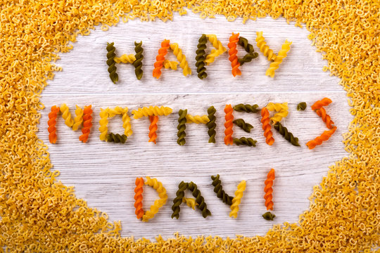 Happy Mother`s Day pasta inscription. Words made from fusilli pasta. Creative greeting by using food. Unusual surprise for mom.