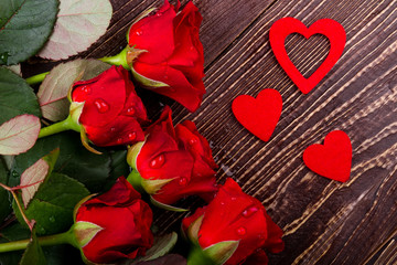 Roses with water drops. Fresh flowers near hearts. Create festive mood. Template of romantic gift.