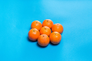 Sun symbol from Six Colorful fresh orange mandarins laid out on blue table viewed  above with copy space