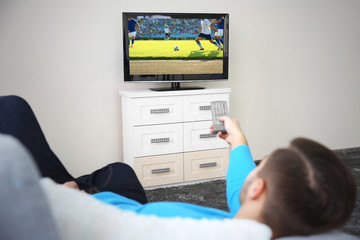 Man watching football game on television at home. Leisure and entertainment concept.