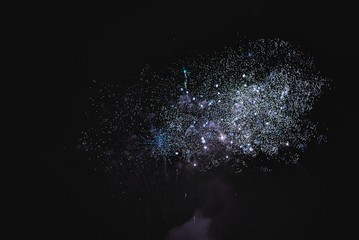 Shiny natural fireworks on dark sky background with little smoke