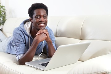 African-American man with laptop.