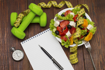 Dumbbell, vegetable salad and measuring tape on rustic wooden table.