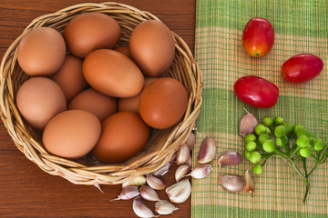 Raw organic brown eggs in wicker basket with ingredients put on bamboo mat and wood table