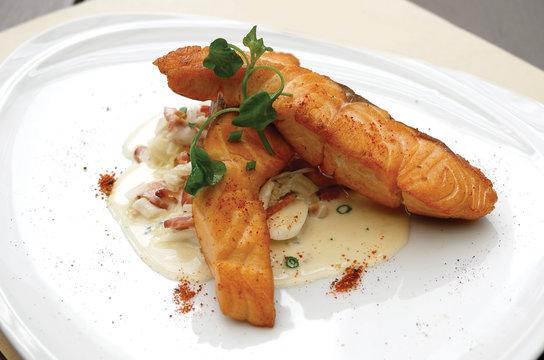 Close up of seared salmon with leek carbonara sauce. Selective focus.
