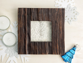 dark wooden photo frame with candles and snowflakes on wood