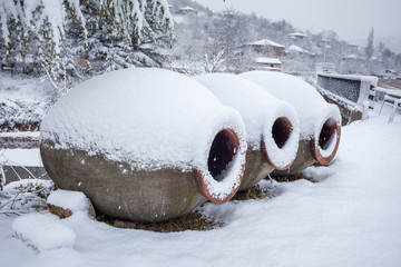 Snow covered georgian jugs for wine, outdoor in winter
