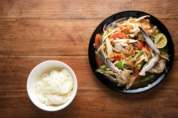 spicy papaya salad with crab and thai Vermicelli, chopsticks, on wooden table, Thai food