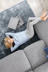 Fototapeta Relaks po zakupach.Kobieta wypoczywa na dywanie.  obraz