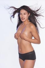 Junge Asiatin mit samtig weicher haut und wehenden Haaren, die Ihre nackten brüste mit den Händen verdeckt.