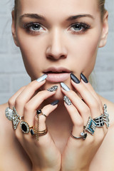 beauty face.woman's hands with jewelry rings.beautiful girl with make-up and manicure