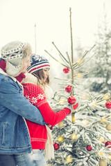 Pärchen schmückt den Weihnachtsbaum zusammen