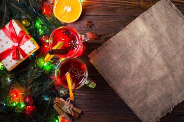 Two glasses,cup of red hot drink.Mulled wine on wooden background with christmas spices,orange slice,close up.Christmas mulled wine.Branch of Christmas tree, Christmas lights,copy space