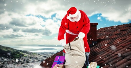 Composite image of santa claus filling gift boxes in sack