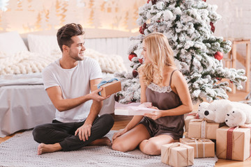 Handsome pleasant man giving a Christmas gift to his girlfriend