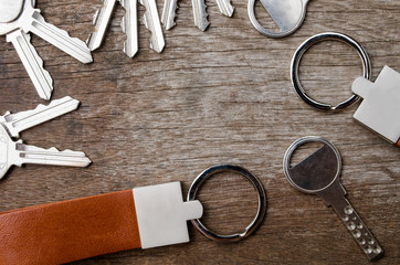 House key on wooden background with leather key chain on wooden