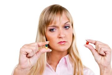 frau schaut skeptisch auf tabletten