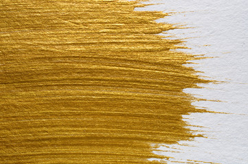 Gold acrylic paint on white paper background , gold texture free