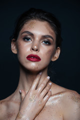 Beauty portrait of pretty young woman with glitter makeup