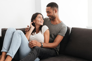 Photo of beautiful couple laughing on a sofa at home