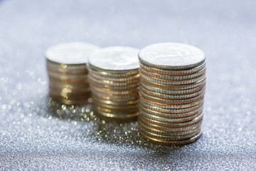 Selective focus of stack of US. dollar coins with silver glitter