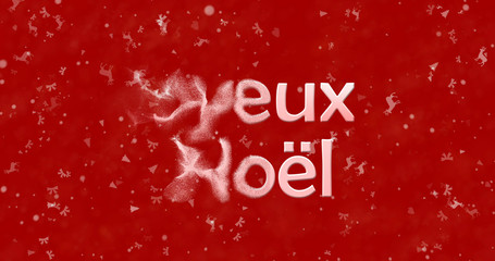 "Merry Christmas text in French ""Joyeux Noel"" turns to dust from left on red background"