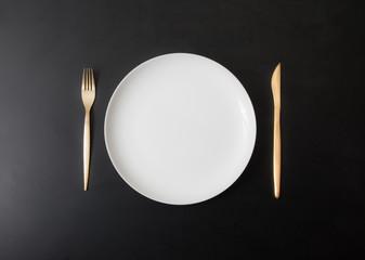 piatto e posate su fondo scuro