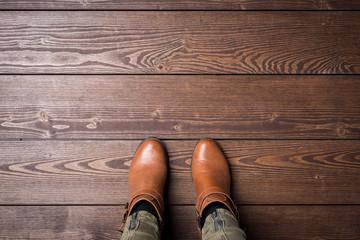 Woman in winter shoes standing on wooden floor