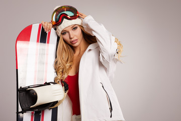 Woman with a snowboard, studio shoot. Grey background