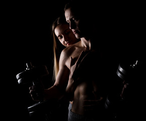 beautiful young sporty sexy couple showing muscle on a dark background