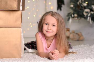 girl child with box of Christmas gift lying on floor