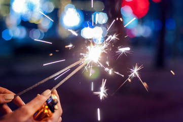 Close up of woman holding sparkler at night.