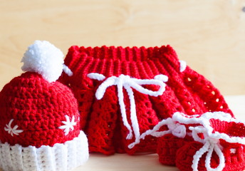 Knitting. Christmas hat, skirt, baby's bootees, close up
