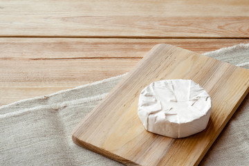 Sliced round camembert cheese on a wooden board. Rustic style and natural light. Top view. Vintage burlap napkin background.