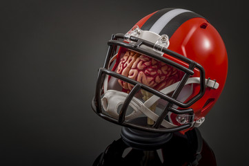American football concussion protocol concept with a brain wearing a football helmet for protection with copy space