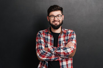 Happy man standing over chalkboard with arms crossed