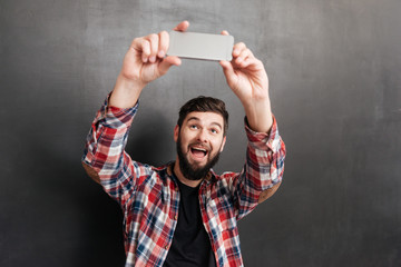 Happy bearded young man making selfie with mobile phone
